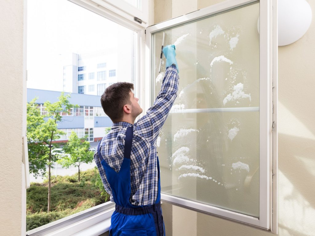 residential-window-cleaner-working-on-cleaning-a-window-pane
