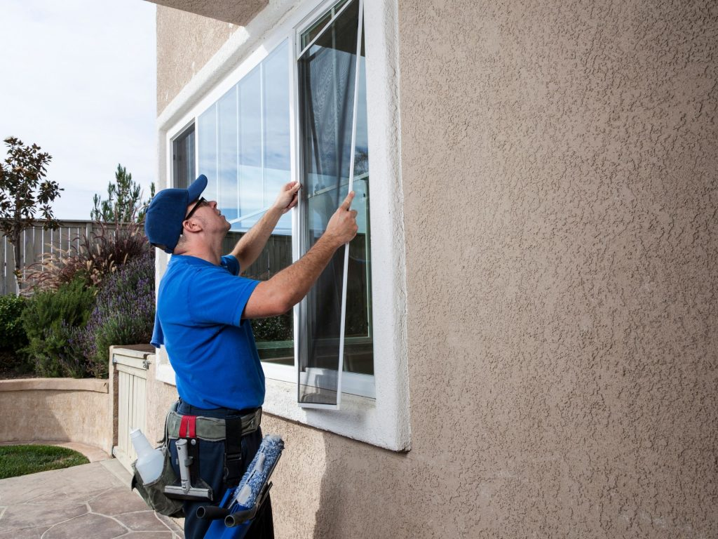 man-replacing-window-screen-into-the-frame